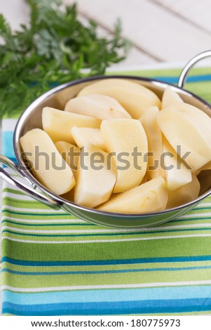Peeled potato in bowl on white wooden table. Selective focus. - stock photo