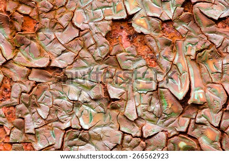 Peeling brown green paint reveals the texture of the rust beneath. - stock photo
