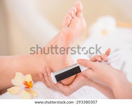 Peeling feet pedicure procedure in a beauty salon. - stock photo