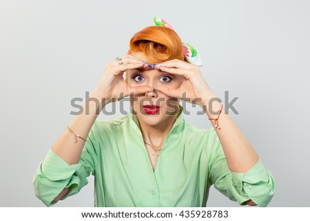 Peering. Closeup portrait young pretty happy woman peeking through her fingers like binoculars searching for something looking to the future at the camera isolated gray grey background. Sign symbols - stock photo