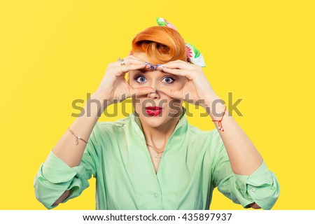 Peering concept. Closeup portrait young pretty stunned curious woman peeking looking through fingers like binoculars searching for something looking to the future at camera isolated yellow background - stock photo