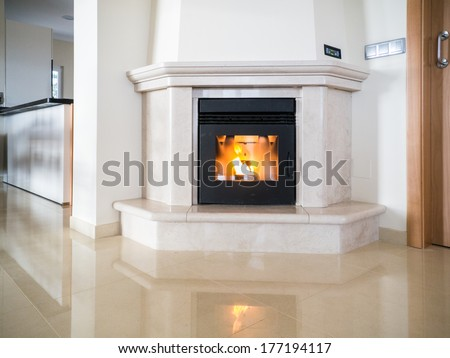 Pellet fire place alight and reflecting in a polished stone floor - stock photo