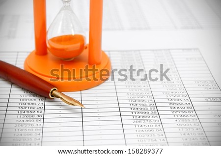 Pen, a sand-glass and documents. - stock photo