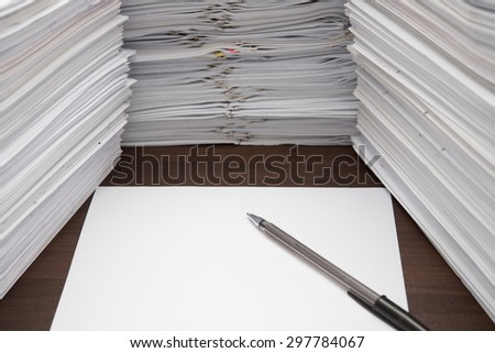 pen and blank paper besides piles of documents - stock photo