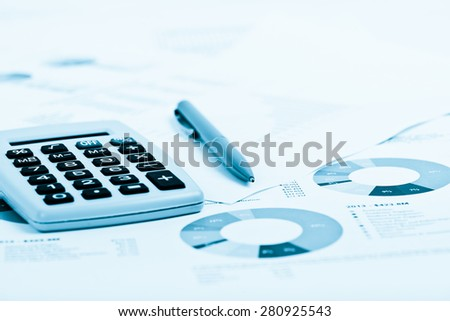 Pen and Calculator on a paper with graph and charts.  Blue toned - stock photo