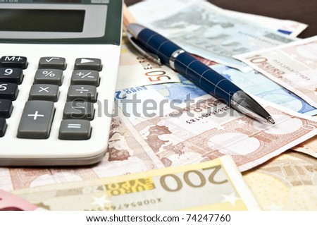 Pen and calculator on euro banknotes - stock photo