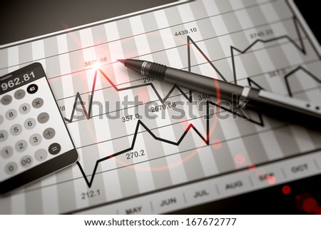 Pen and calculator on stock chart - stock photo