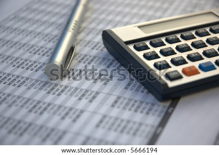 pen and calculator on the paper tables - stock photo