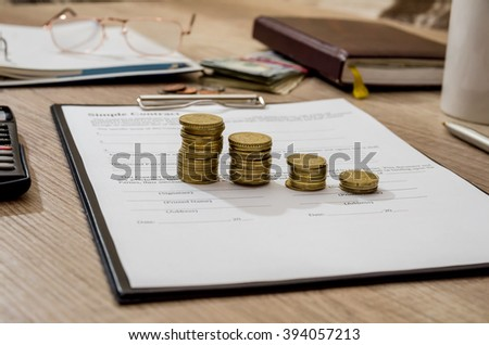 Pen and contract papers, calculator, coin on wooden desk - stock photo