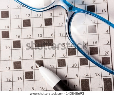 Pen and glasses on the newspaper with crossword - stock photo