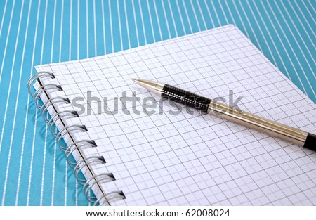 Pen and graph paper notebook on a blue lined tabletop - stock photo