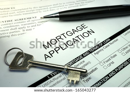 pen and key on mortgage application form - stock photo