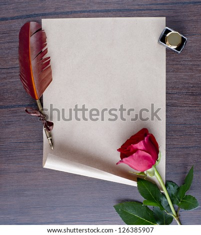 pen and old paper with a rose on a wooden table - stock photo