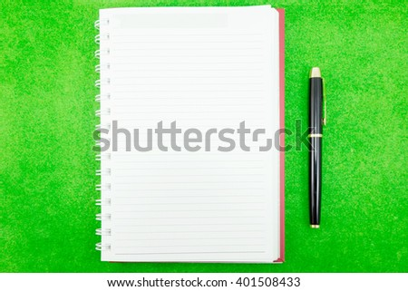 pen and paper notebook on green background - stock photo