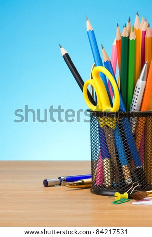 pen and pens in holder on blue background - stock photo