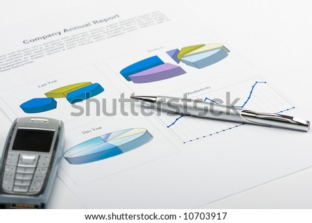 pen and phone laying on report with diagrams - stock photo
