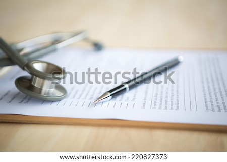 Pen and stethoscope on Patient information - stock photo