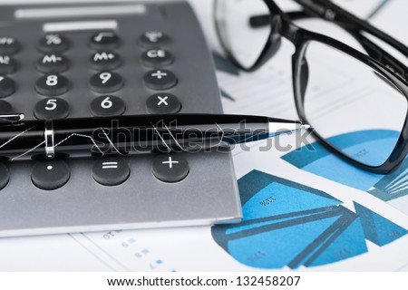 Pen, calculator and glasses on a background of diagrams.Business concept - stock photo