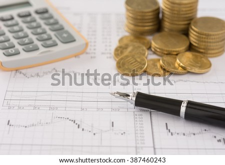 pen ,calculator, money with the report analyzes stock market trends put on desk's investor. selective focus. investment concept - stock photo