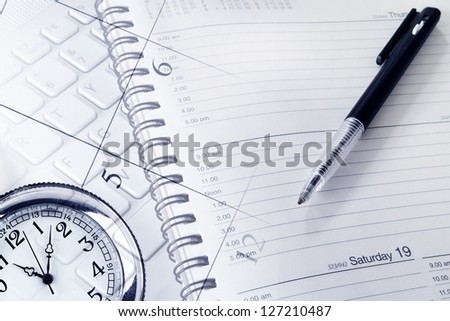 Pen, clock, diary, calendar page and keyboard - stock photo