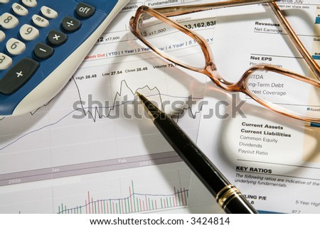 Pen, eyeglasses and calculator over business-stock report - stock photo