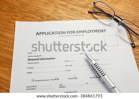 pen,eyeglasses on business  document application form and  wood background. - stock photo