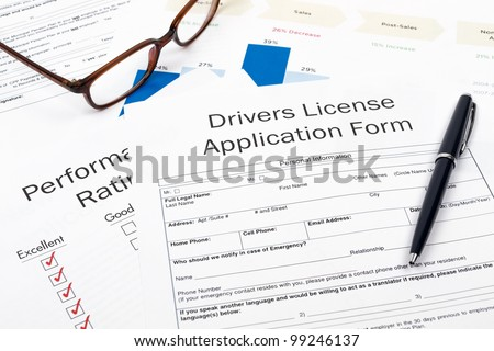 Pen, Glasses and Drivers License Application Form on desktop in business office. - stock photo