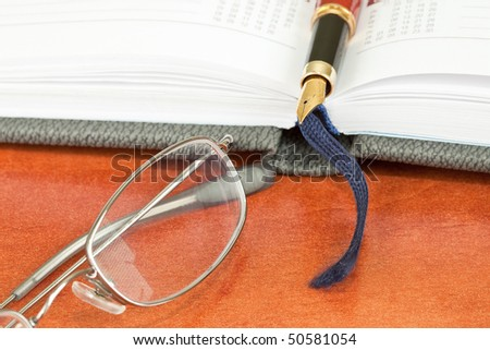 Pen, glasses and notebook on desk - stock photo