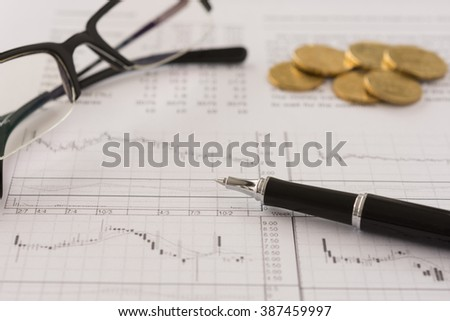 pen ,glasses, money with the report analyzes stock market trends put on desk's fund manager. selective focus. - stock photo
