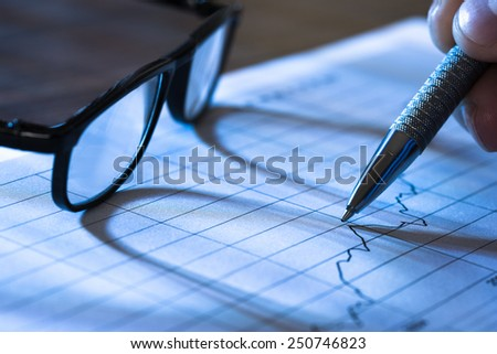 Pen In Hand Pointing At Graph On Paper With Glasses - stock photo