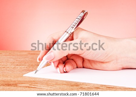 pen in hand writing on paper - stock photo