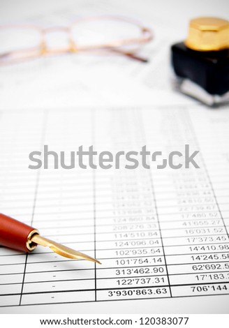 Pen, ink and glasses on the documents. - stock photo