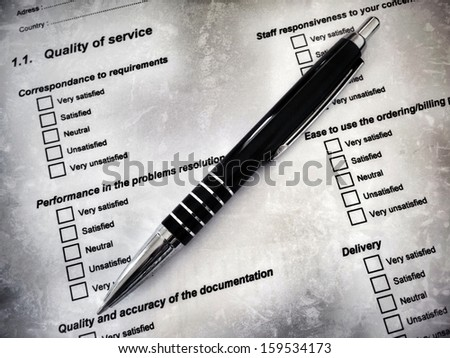 Pen laying on a customer satisfaction form, referring to concepts such as marketing survey, assessment, criteria, quality of products or services, as well as administration and form filling - stock photo