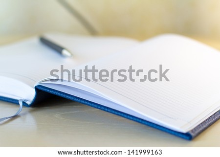 pen lying on opened notebook for notes - stock photo