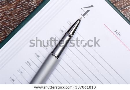 Pen lying on page 4 July datebook - stock photo
