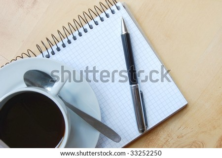 pen, notebook and cup of coffe on the desk - stock photo