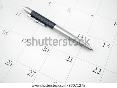 Pen on a calendar page - stock photo