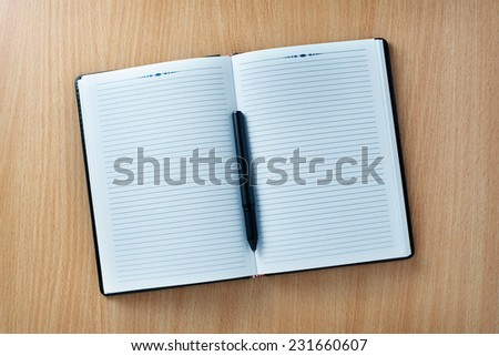 Pen on an open agenda or notebook with blank pages on a wooden table or desk, high-angle close-up - stock photo