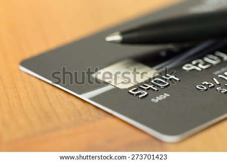 Pen on black credit card - stock photo