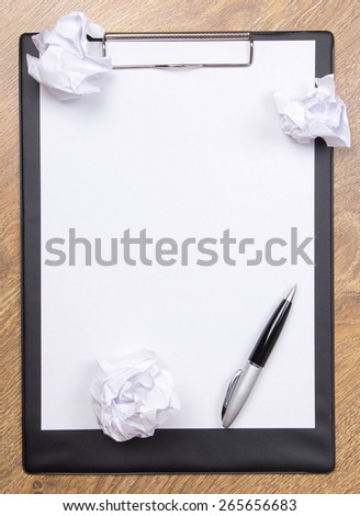 pen on clear white paper with crumble paper balls on wooden table background - stock photo