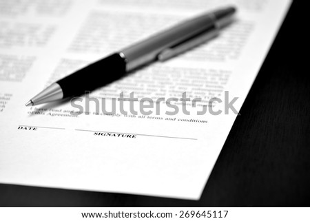 Pen on contract deal paper with blank line for signature to close agreement - stock photo
