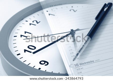 Pen on diary page and clock - stock photo