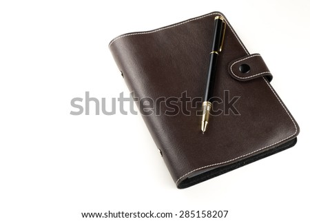 pen on notebook on white isolated background - stock photo
