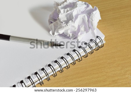 Pen on notebook paper was crumpled on the wooden table . - stock photo