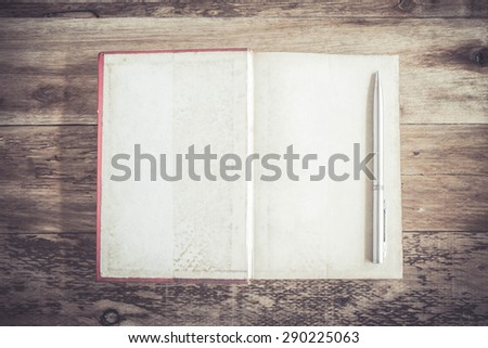 Pen on Open Book blank on old wooden background - stock photo