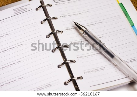 pen on schedule book - stock photo