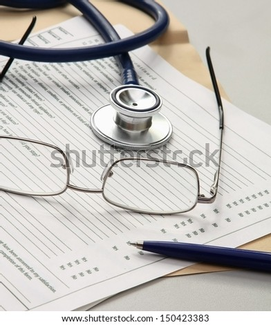 Pen ,stethoscope , folder with papers and glasses - stock photo