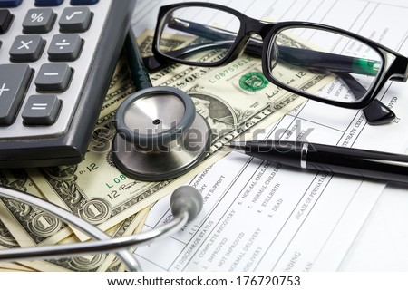 Pen stethoscope glasses and dollar on blank Patient information - stock photo