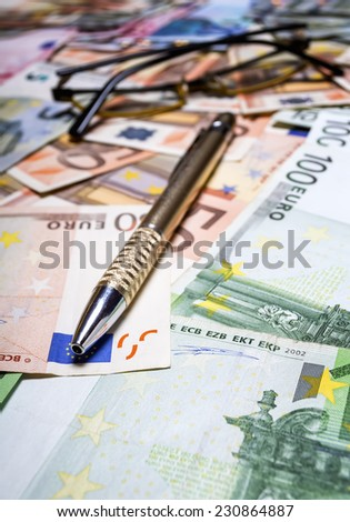 Pen with euro banknotes. Shallow depth of field.  - stock photo