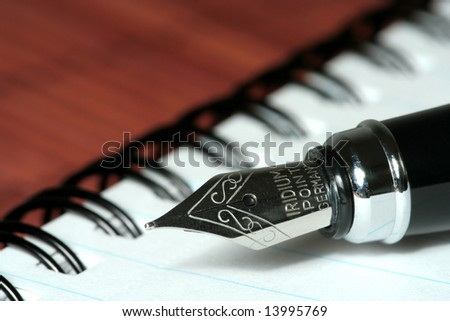 pen with notebook on brown bamboo mat - stock photo